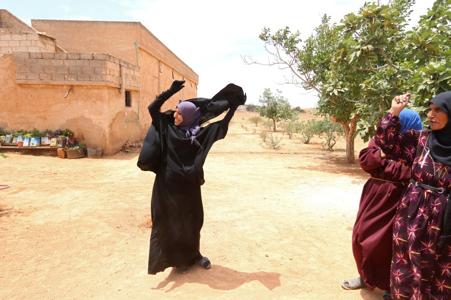 Une femme retire son niqab qu'elle portait après que les Forces démocratiques syriennes ont chassé les dihadistes de Daesh.