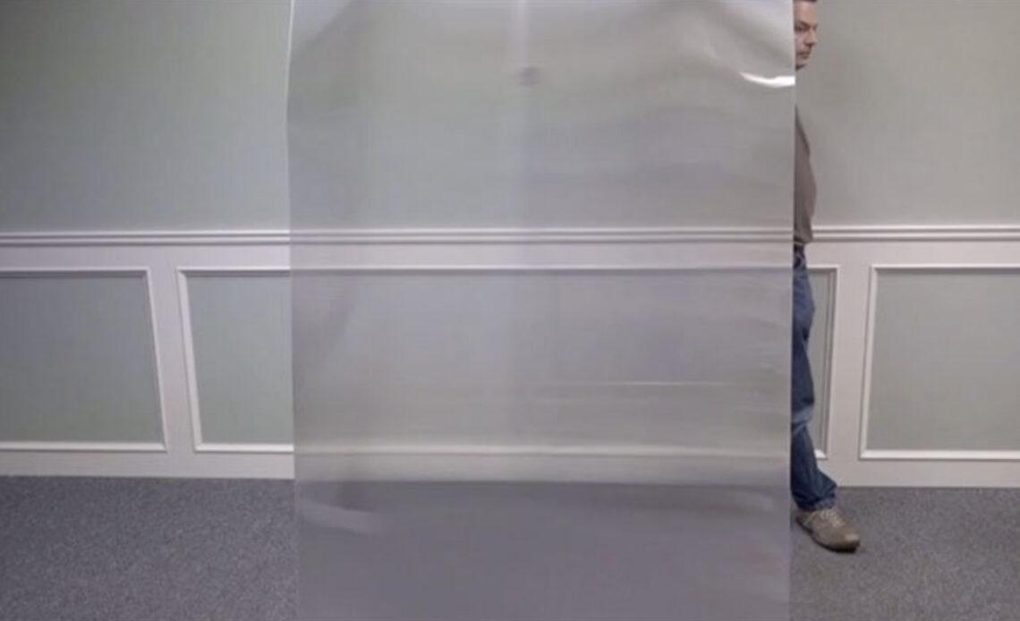 Un homme quasi invisible en passant derrière une plaque transparente