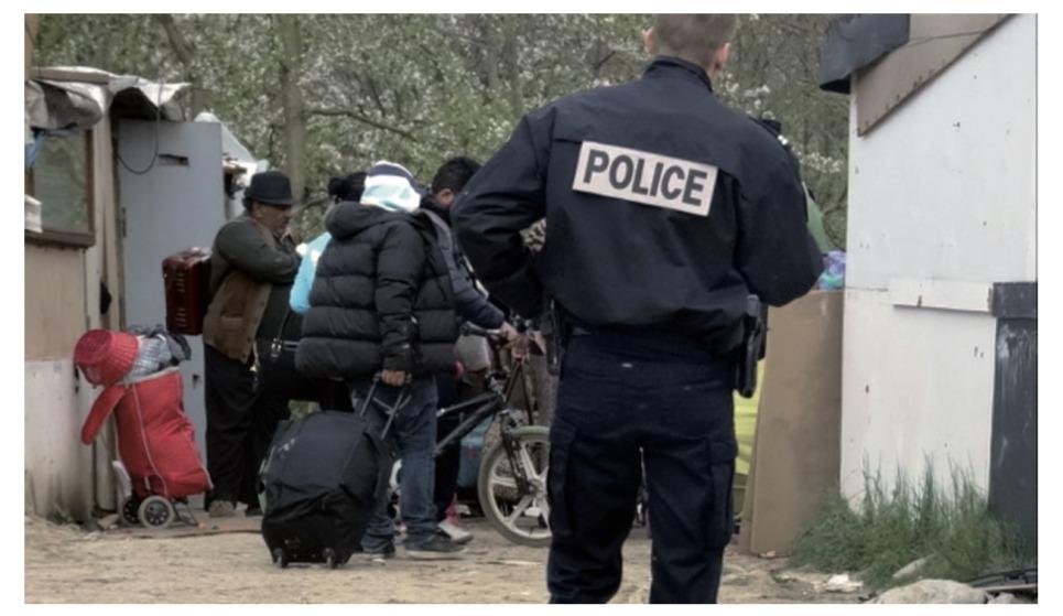Photo d'illustration avec des expulsés et un policier en premier plan